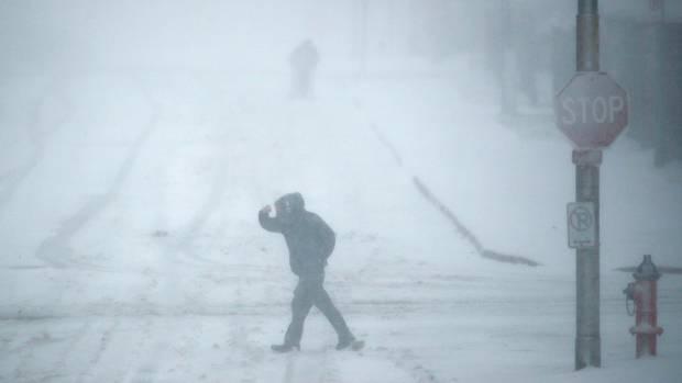 Ein Fußgänger geht in Kansas City bei Schneetreiben über eine Straße.
