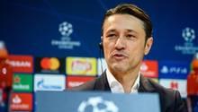 Niko Kovac sitzt auf einem Podium mit Champions-League-Loho und hört mit Knopf im Ohr einer Frage zu