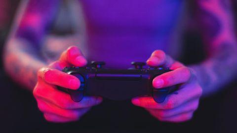 Ein Gamer hält eine Playstation-Konsole in den Händen
