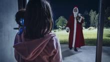 Eine sprechende Puppe führt Kinder in der Nacht ins Wohnzimmer, wo sie den Weihnachtsmann erwarten