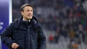 In dunkelblauer Winterjacke steht Niko Kovac am Spielfeldrand und grinst beim Blick auf den Spielstand