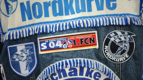 """Ein Fan des FC Schalke 04 trägt eine Jeansjacke mit Aufnähern, darunter """"Nordkurve"""""""