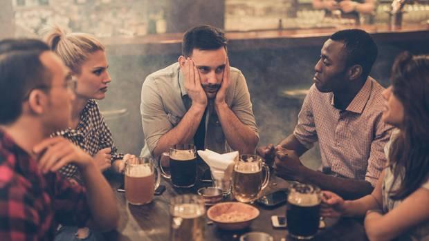Personen in Bar an Tisch