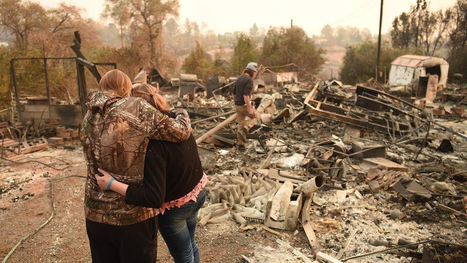 Eine Ehepaar und seine Tochter stehen vor den Überresten ihres verbrannten Hauses in der kalifornischen Kleinstadt Paradise