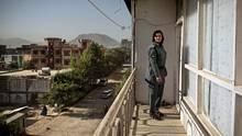 Schamila steht in Uniform auf dem Balkon ihrer Wohnung. Im Hintergrund kann man die Berge des Hindukuschs erkennen. Schamila wurde als Zwölfjährige entführt und von Afghanistan nach Pakistan verschleppt.