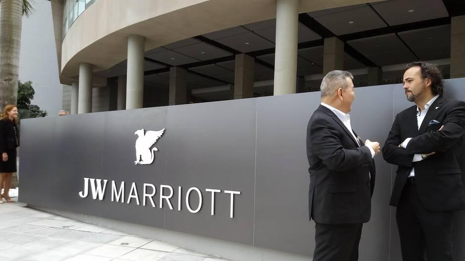 """Auf einer silbergrauen Metallwand ist der weiße Schriftzug """"JW Marriott"""" zu sehen. Daneben stehen zwei Männer in Anzügen"""
