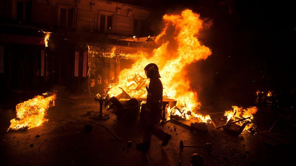 """In Paris geht ein Polizist an einem brennenden Haufen Stühle vorbei. Rund um die Champs-Élysées kam es am Samstagzu heftigen Krawallen bei Demonstrationen der """"Gelben Westen""""."""
