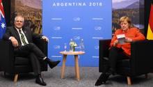 Angela Merkelinformiert sich über Scott Morrison, während dieser schon neben ihr sitzt