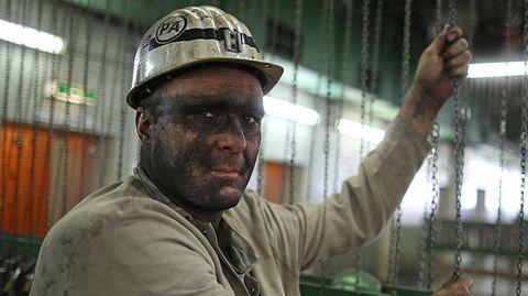 Ein Bergmann mit Helm steht in einem Steinkohlebergwerk