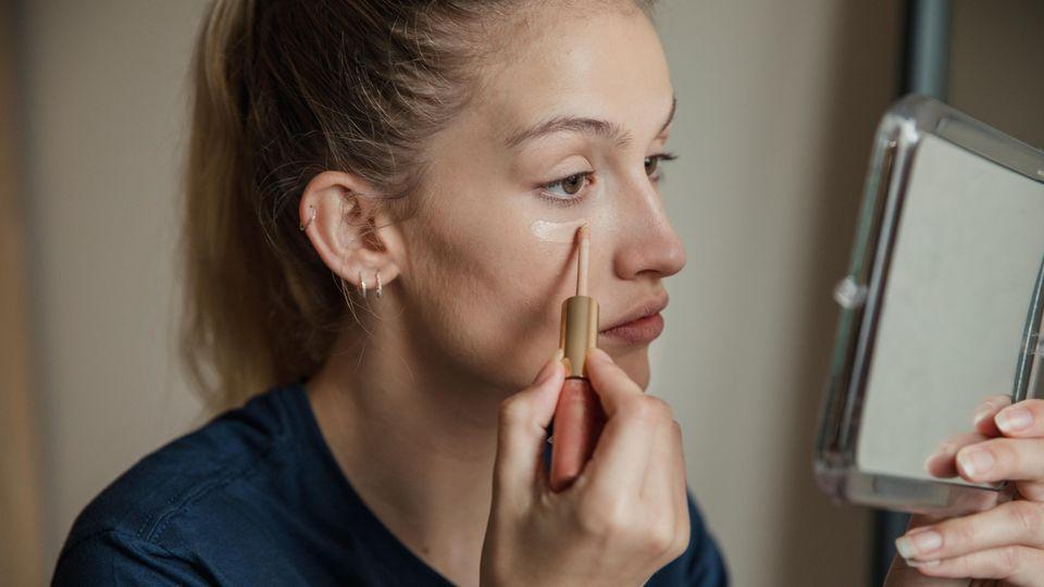 Eine Frau schminkt sich vor einem Spiegel