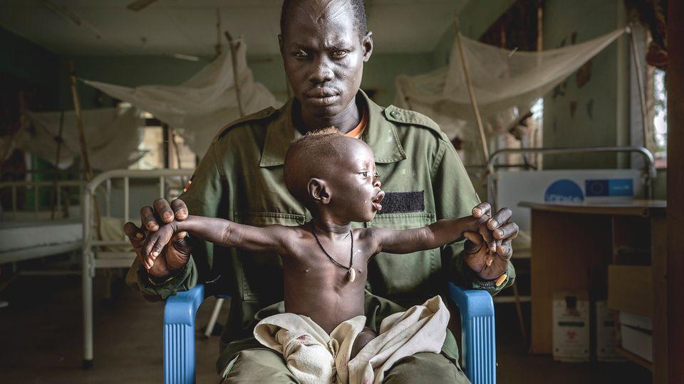 Ein Soldat mit seinem unterernährten Sohn