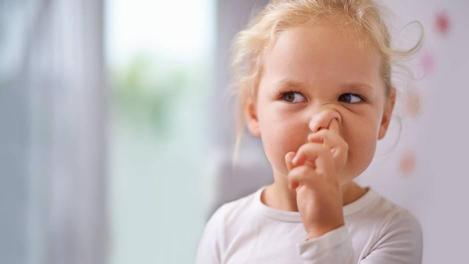 Ein Mädchen bohrt sich in der Nase