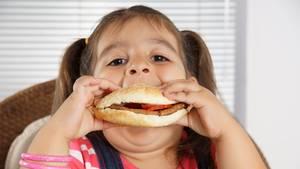 Ein übergewichtiges Mädchen beißt in einen Burger