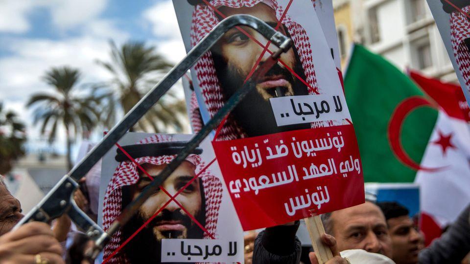 """""""Du bist nicht willkommen"""", heißt es auf diesen Plakaten: InTunesiens Hauptstadt Tunis demonstrierten in der vergangenen Woche Menschen gegen den saudischen Kronprinzen Mohammed bin Salman. Er machte auf seinem Weg zum G20-Gipfel Station in Tunis."""