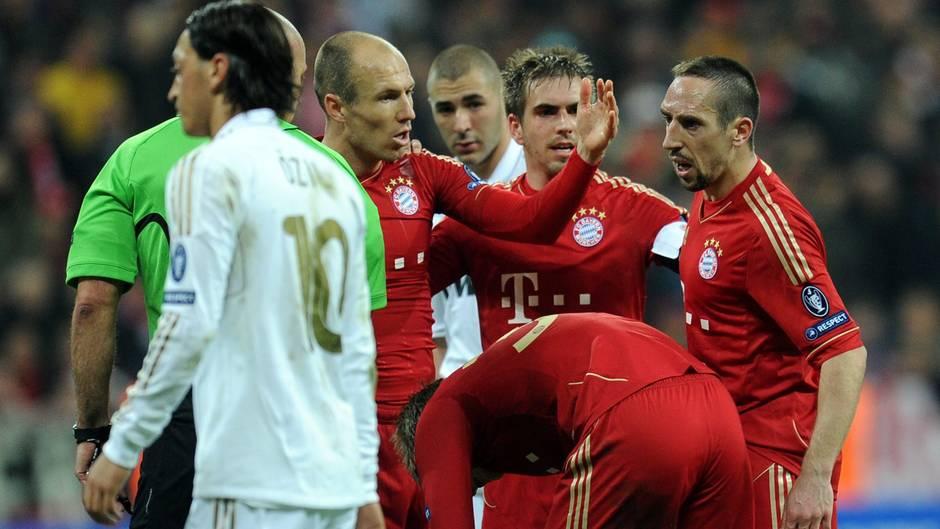 Robben und Franck Ribéry (r.) beäugen sich in den ersten Jahrenganz genau. Der Konkurrenzkampfgehtsogar soweit,dass Ribéry dem HolländereineBackpfeife verpasst. Was warpassiert? Im Hinspiel des Champions-League-Halbfinales gegen Real Madrid im April 2012 willRibéry einen Freistoß treten, doch Robben drängtihn zurück, weil Toni Kroos ran sollte (im Bild gebeugt, im Vordergrund trottet ein junger Mesut Özil im Real-Trikot vorbei).So geschiehtes, der blutjunge Kroos schießt jedoch mitten in die Mauer. Ribéry ist daraufhin so sauer, dass er seinem Teamkollegen Robben in der Pause eine knallt. Der Niederländervergibt ihm später, und die ÄraRobbery nimmt weiter an Fahrt auf.