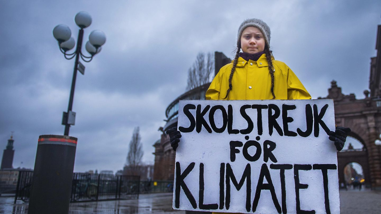 Greta Thunberg mit Schild vor dem Parlament.
