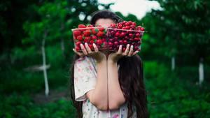 Frau hält sich Obst vor das Gesicht