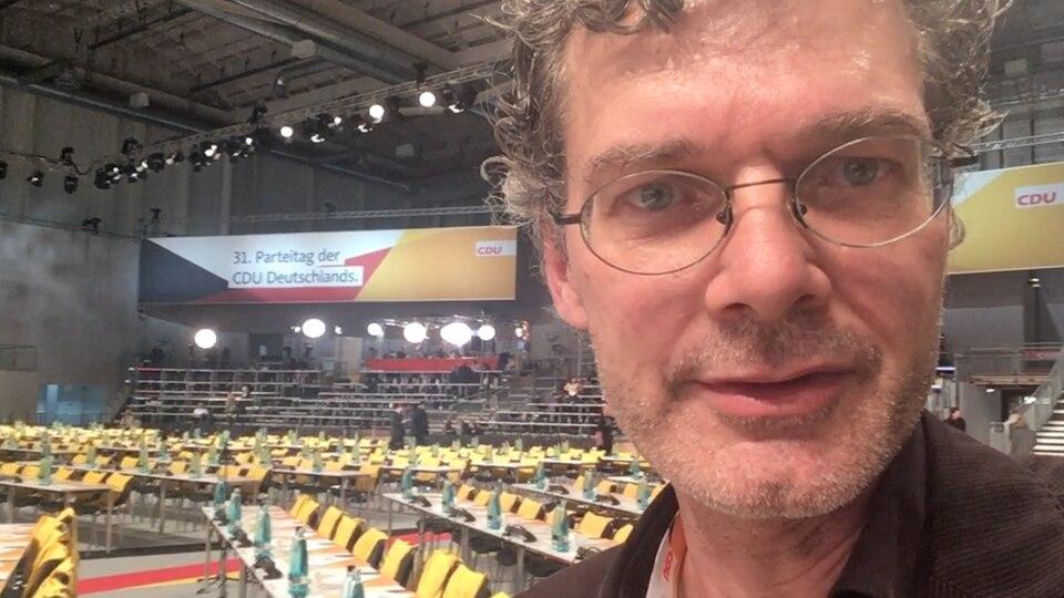 stern-Reporter Tilman Gerwien steht in der Halle des CDU-Parteitags 2018 in Hamburg vor noch leeren Stuhlreihen