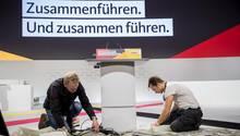 Arbeiter bereiten das Rednerpult in der Hamburger Messehalle für den CDU-Bundesparteitag vor