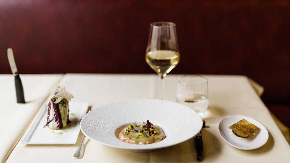 Ein Kreis hauchzart gegarter Lachsscheiben unter einer buttrigen Miesmuschelsauce, dazu Salat
