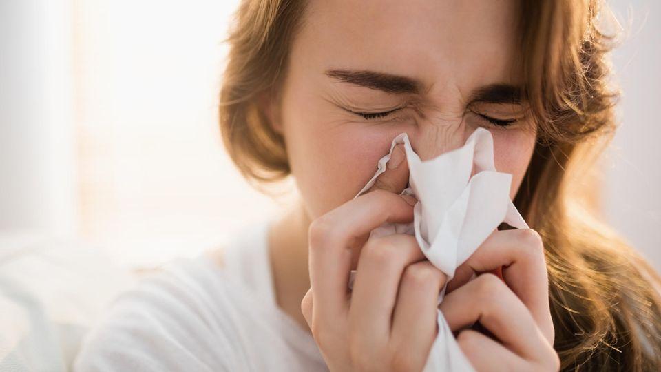 Eine Frau ist erkältet und hält ein Taschentuch vor das Gesicht