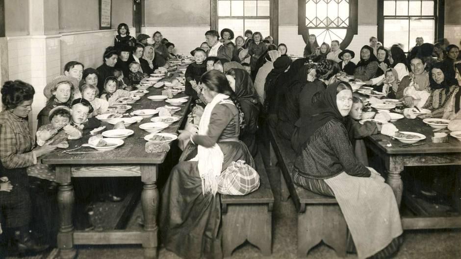 Frauen und Kinder beim Essen auf Ellis Island, 1902-1913 (Edwin Levick)