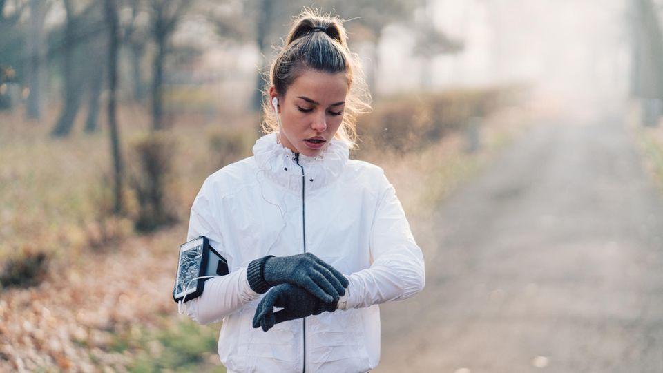Eine junge Frau joggt im Winter durch einen Park