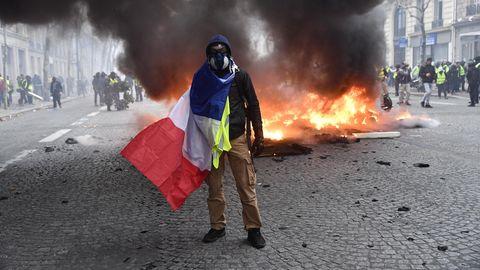 """Paris, achtes Arrondissement: Ein """"Gelbwesten""""-Demonstrant posiert mit einerfranzösischen Fahne vor einem brennenden Auto für die Kamera. Die Wut der Protestbewegung richtet sich aber auch gegen Präsident Macron und dessen Reformpolitik."""