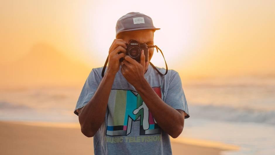 Fotograf mit Kamera am Strand