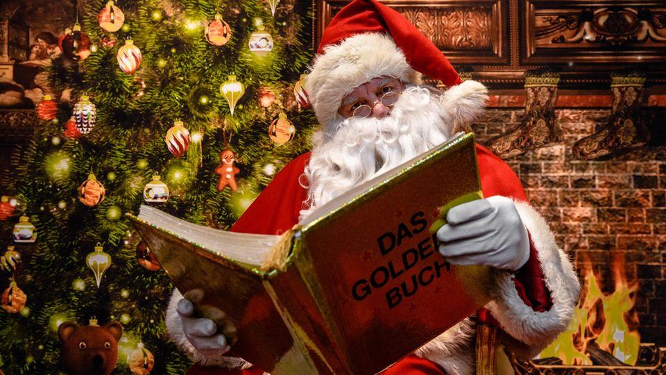 Ein Weihnachtsmann - hier ein Exemplar aus Schleswig-Holstein -liest aus einem goldenen Buch