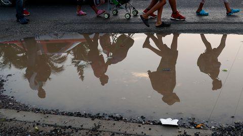 Migranten aus Mittelamerika spiegeln sich in einer Pfütze am Straßenrand. Sie sind Teil einer Gruppe tausender Menschen, die aus Mittelamerika vor der Gewalt durch Jugendbanden und der schlechten wirtschaftlichen Lage in der Region fliehen und sich auf dem Weg in die USA befinden.