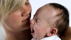 Ein Elternpaar sitzt erschöpt im Babybett ihres Kindes