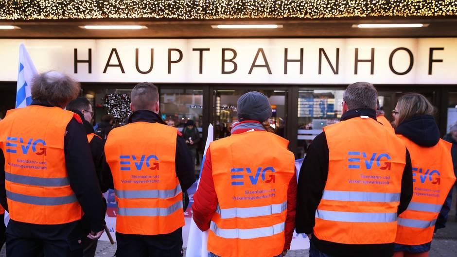 """Fünf Männer in orangen Warnwesten mit EVG-Logo stehen vor einem """"Hauptbahnhof""""-Schild"""