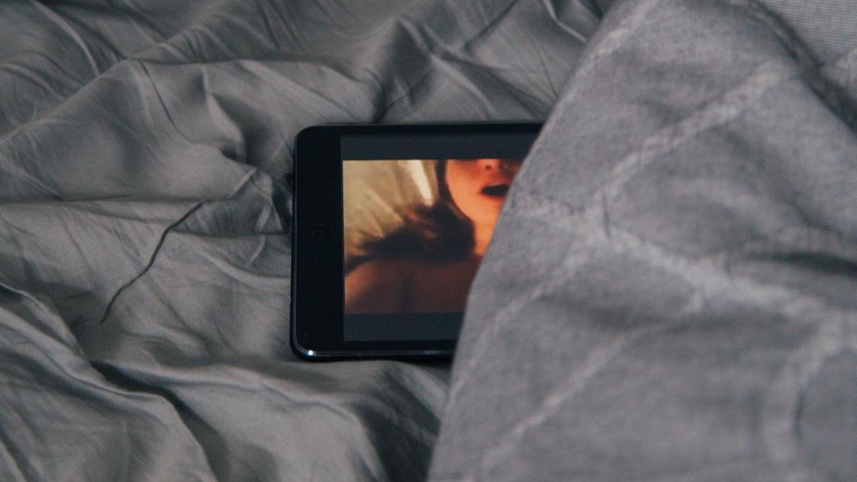 Handy mit Porno in einem Bett