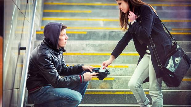 Frau spendet Geld an Obdachlosen