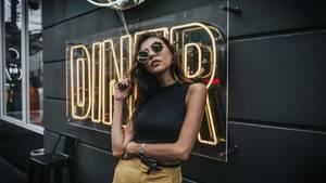 Frau posiert vor einer Wand