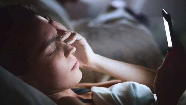 Eine Frau liegt im Bett und blickt auf ihr Smartphone