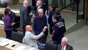 Der AfD-AbgeordneteStefan Räpple (sitzend) spricht im baden-württembergischen Landtag mit Polizisten. Zuvor hatte er sich geweigerttrotz Aufforderung der Landtagspräsidentin den Saal zu verlassen.