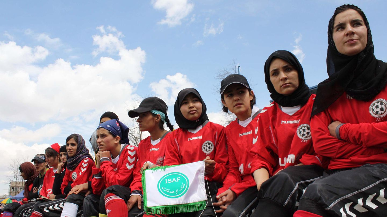 Die afghanische Frauenfußballmannschaft sitzt in einer Reihe.
