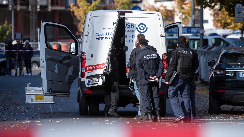 Polizeibeamte stehen an einem Geldtransporter mit aufgebrochenen Türen