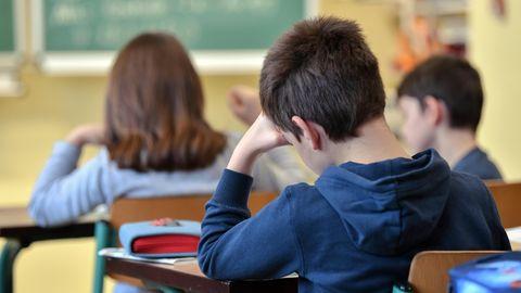 Schüler sitzt mit abgestützter Hand in Schulklasse