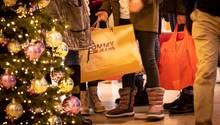 Menschen stehen mit Einkaufstüten in einem Kaufhaus