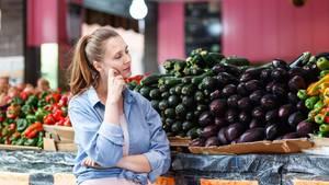 Eine Frau steht vor einem Gemüsestand