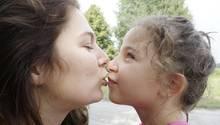 Eine Mutter will ihre kleine Tochter küssen