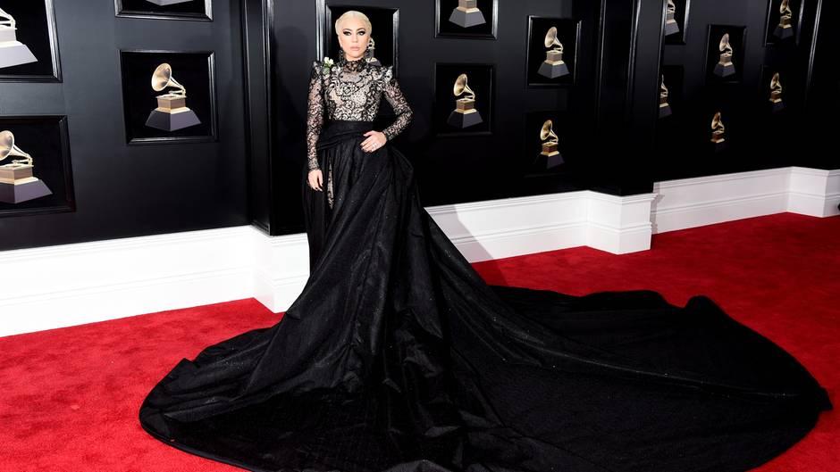 """Grammy-Verleihung, New York  Was für ein Auftritt! Sängerin Lady Gaga erschien zur 60. Grammy-Verleihung in einem Spitzen-Jumpsuit, der von Unmengen schwarzen Stoffs umhüllt wurde. Die opulente Kreation stammt von Armani Privé. Wichtiger war jedoch ein Detail an Gagas rechter Schulter. Dort trug die Musikerin aus Solidarität mit der """"Time's Up""""-Bewegung eine weiße Rose - wie so viele andere Stars an diesem Abend."""