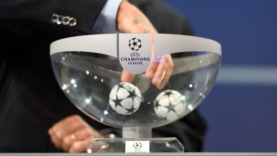 """Eine Männerhand greift in einen Lostopf mit """"Champions League""""-Logo, in dem noch zwei Kugeln kreiseln"""