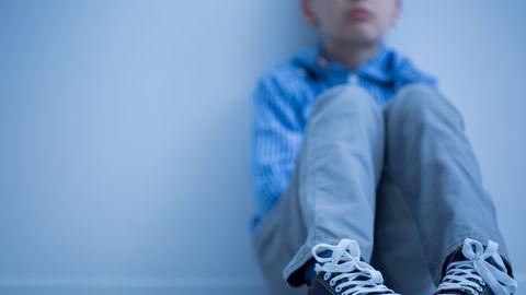 Junge sitzt auf dem Boden