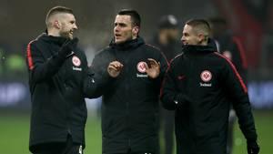 Drei Spieler von Eintracht Frankfurt gehen in dicken Parkas über den Platz und unterhalten sich dabei