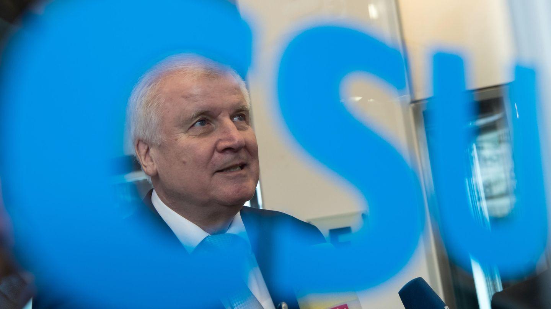 Auf einer Glasscheibe steht ein blauer CSU-Schriftzug. Durch das C ist dahinter Horst Seehofers Gesicht zu sehen