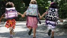 Drei Kinder mit Schulranzen rennen